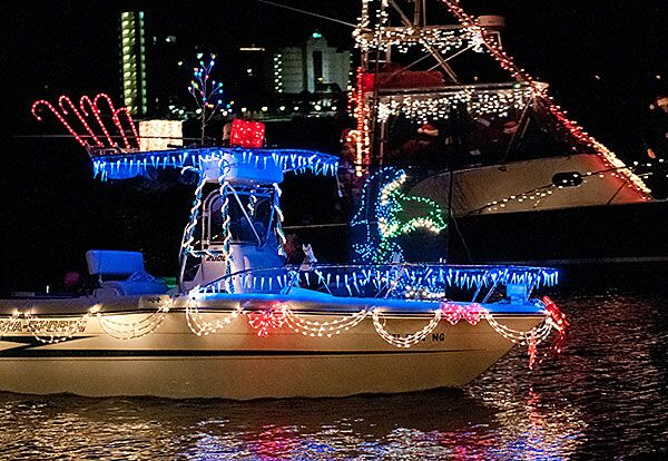 small yacht decorated with christmas lights
