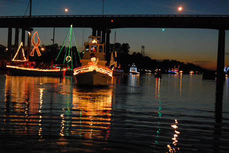 boats decorated with lights pass underneath a bridge