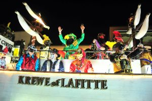 masked men in pirate costumes ride aboard a parade float with Krewe of Lafitte written on the side