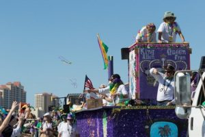 beads fly off a float as it parades through Gulf Shores, AL
